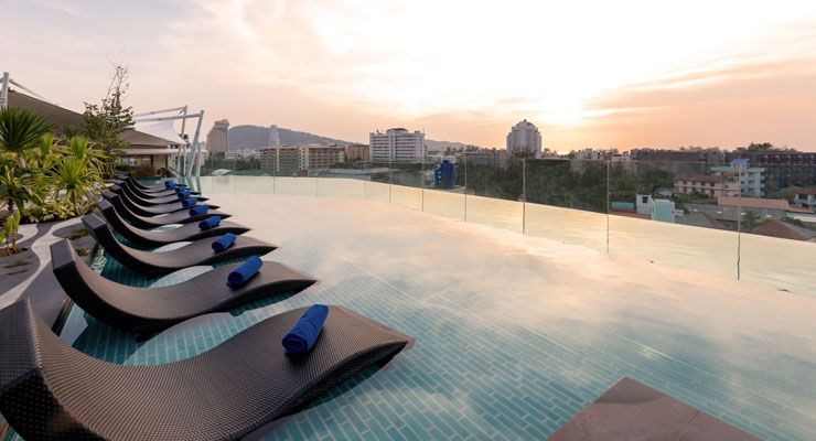 Oakwood Hotel Journeyhub Phuket offers an infinity pool with a tropical garden backdrop and sea view