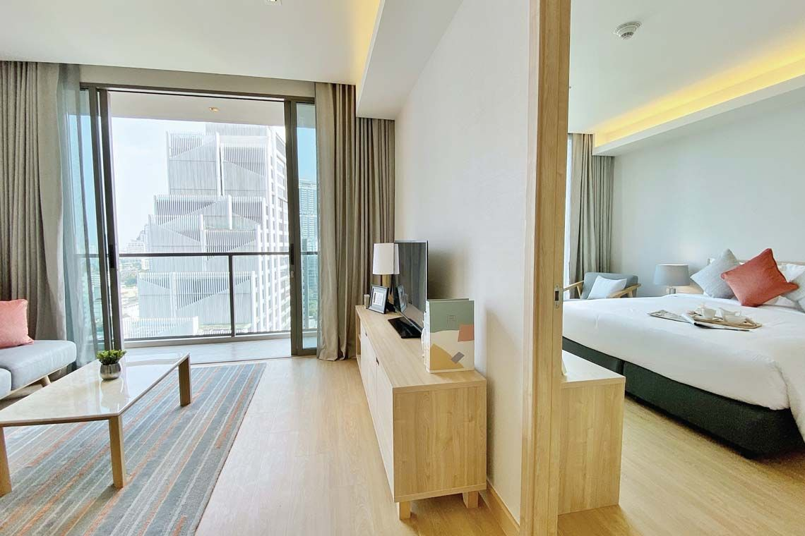 Oakwood Suites Bangkok's one-bedroom superior apartment's bedroom and living room