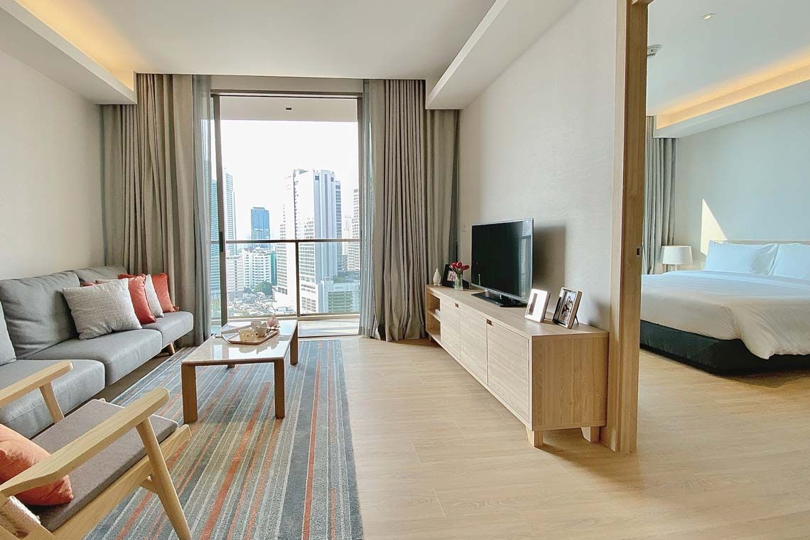 Oakwood Suites Bangkok's two-bedroom deluxe's master bedroom and living room