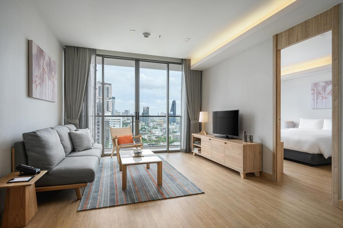 Oakwood Suites Bangkok's one-bedroom deluxe apartment's living area